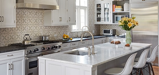 Stylish kitchen with white cabinets and modern white kitchen island in Winnetka