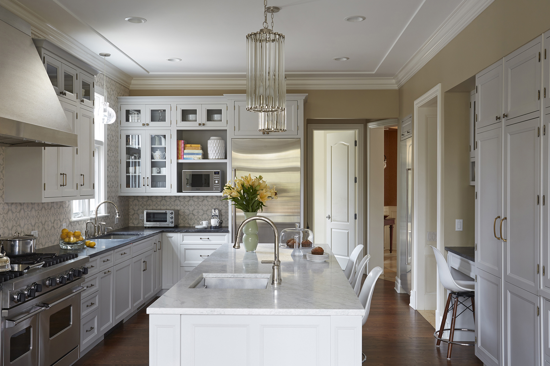 Luxury white kitchen furniture design with large island after remodeling in Winnetka