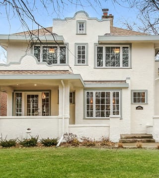 House exterior remodel with classic style cream stucco and sage gray trim in Wilmette