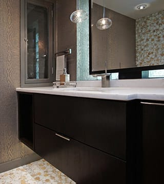 Lake Forest bathroom design with dark brown finish, accent wallpaper, two tone floor tile