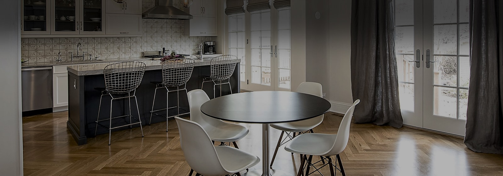 Fashionable kitchen eating area with floor to ceiling windows four modern chairs sit in Chicago